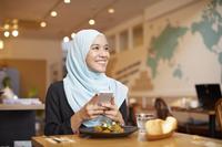 スマートフォンを操作するムスリムの女性