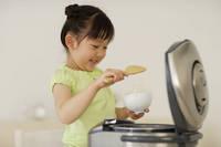 お茶碗にご飯をよそう女の子