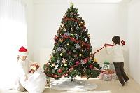 リビングでクリスマスツリーを飾る男の子と女の子