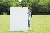 新緑の中ホワイトボードを持つ日本人の女の子