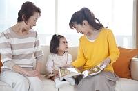 ソファに座る女性3世代親子