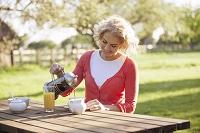 ガーデンでコーヒーを注ぐ外国人女性