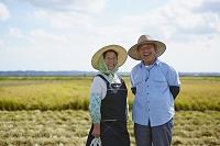 田園に立つ農家の夫婦