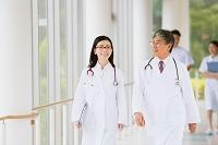 廊下を歩く笑顔の医者と医者