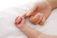 お母さんの指を握る赤ちゃんの手