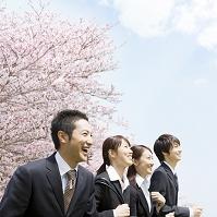 桜の前に立つ新入社員