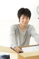 引っ越しの荷造りをする若い日本人男性