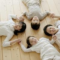 床に寝転び手を繋ぐ日本人親子