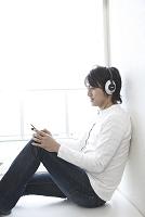 ヘッドフォンで音楽を楽しむ男性