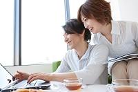 ノートパソコンを見ている中高年夫婦