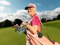ゴルフをするシニア女性