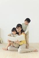 子供達に絵本の読み聞かせをするお母さん