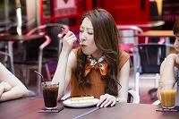 オープンカフェでケーキを食べる女性