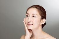 頬に手をあてる中高年日本人女性