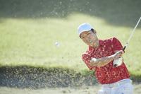バンカーショットを打つ男子ゴルフ選手