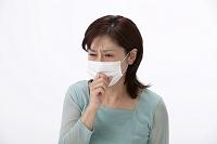 マスクをして咳込む中高年日本人女性