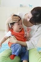 泣く赤ちゃんを抱っこするお母さん