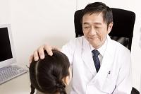 問診診察中の子供と中高年医師