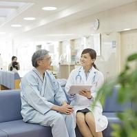 病院のロビーで医者と話をする患者