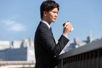 ドリンクを持つ日本人ビジネスマン