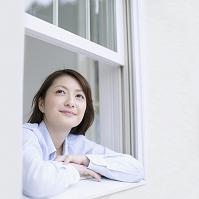 窓から顔を出す日本人女性