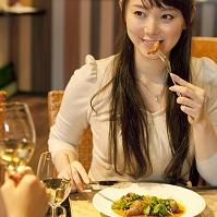 食事をしながら微笑む日本人女性