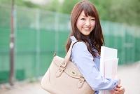 公園の歩道を歩く日本人女性