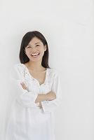白い壁の前で腕を組み笑う日本人女性
