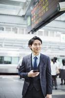 電車を利用する日本人ビジネスマン