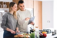 タブレットを見て料理するカップル