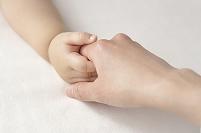 手をつなぐ赤ちゃんと母親