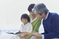孫と絵本を見る祖父母
