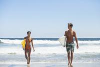 海でサーフボードを持つカップル