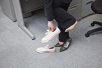 ハイヒールからスニーカーに履き替える女性