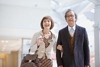 腕を組んで歩く中高年夫婦