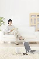 パソコンとスマホのあるリビングでくつろぐ日本人男性