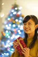 イルミネーションの前でプレゼントを持ち微笑む日本人女性
