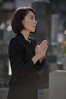 お墓の前で手を合わせる喪服姿の日本人女性