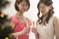 クリスマスツリーとシャンパンで乾杯する女性