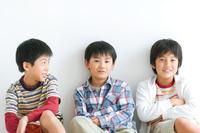 壁にもたれて座る日本人の男の子