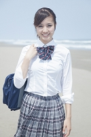 浜辺で微笑む女子高校生
