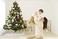 クリスマスツリーのあるリビングで寛ぐママと赤ちゃん