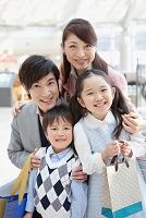 買い物袋を持つ笑顔の日本人家族