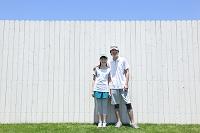 スポーツウェアを着て白い塀の前に立つカップル