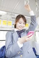電車の中でスマートフォンを持つ女子高校生