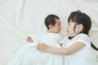 新生児の赤ちゃんを見つめる日本人の女の子
