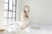 大きな窓のある広い寝室のベッドで起きる日本人女性