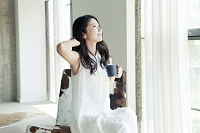 窓辺でくつろぐ20代日本人女性