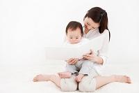 赤ちゃんを抱く母親と絵本