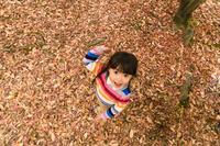 落ち葉のじゅうたんの上に立つ女の子